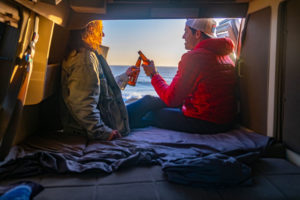 Couple enjoys campervan at sunsert