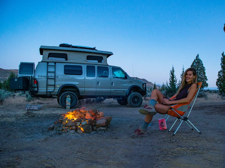 Sitting in a Helinox camp chair in front of a camp fire with Sportsmobile 4x4 Ford Econoline adventure van