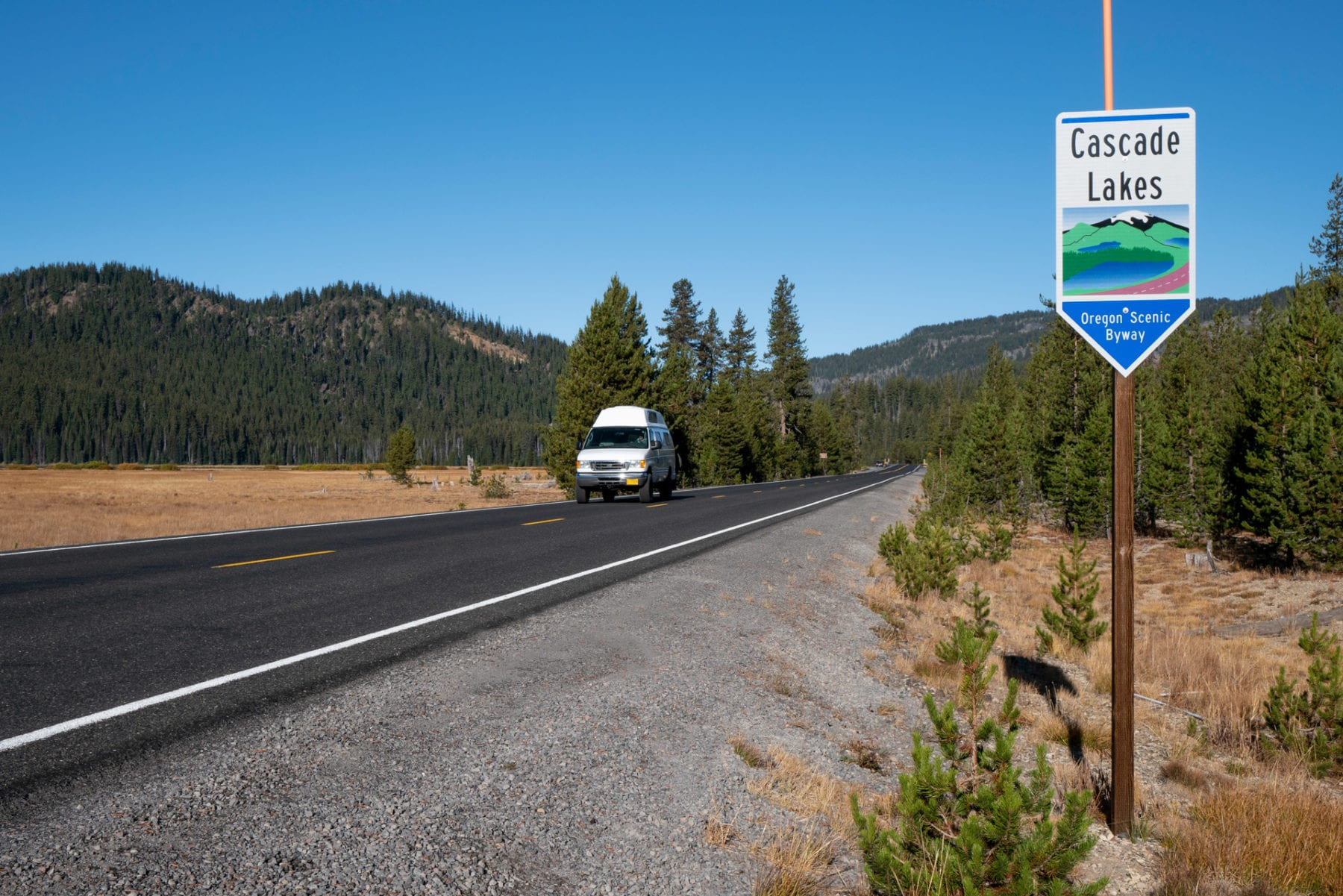 driving down Oregon's Cascade Lakes Scenic Byway in a camper van