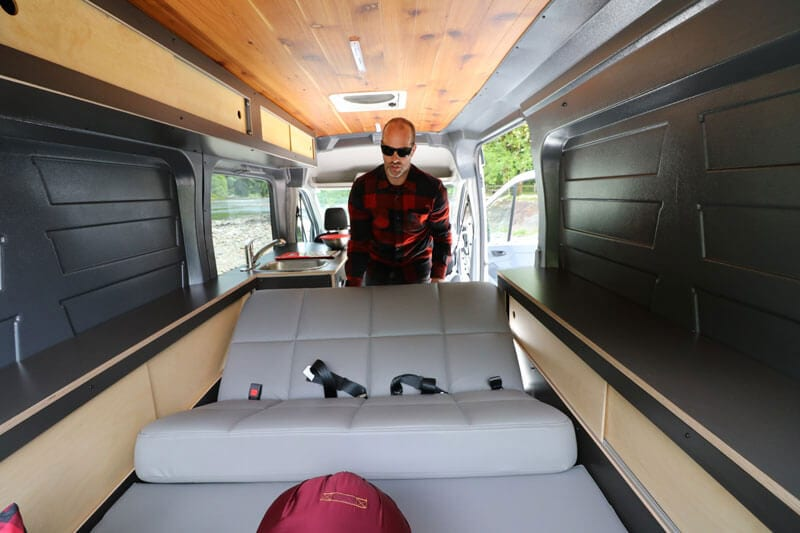 Pulling sofa bed out on adventure camper van