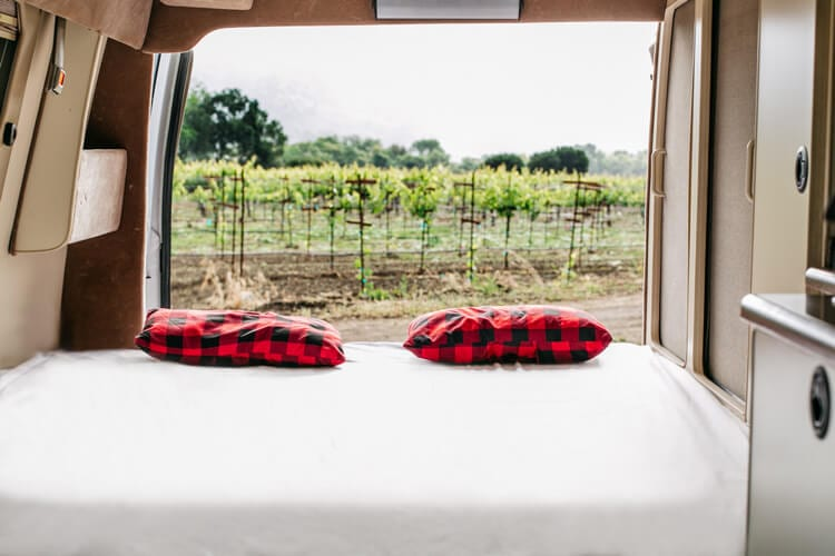 Sofa bed in camper van with camp pillows and Rumpl blanket