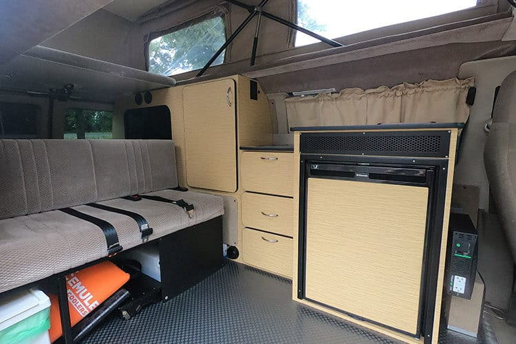 Inside 4wd Ford Econoline camper van conversion with kitchen and sofa bed