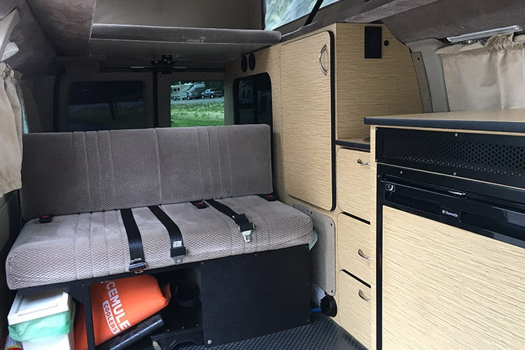 Inside 4wd Ford Econoline sprinter van conversion with kitchen and sofa bed
