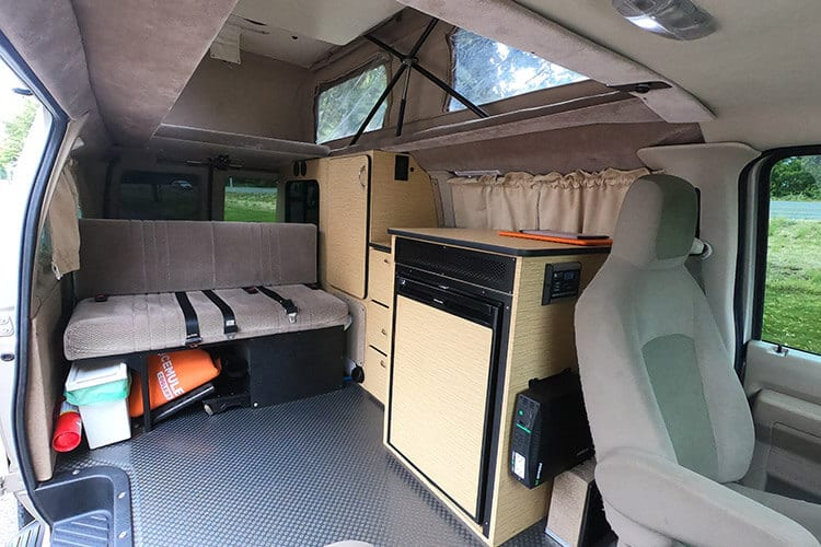 Inside 4wd Ford Econoline adventure van conversion with kitchen and sofa bed