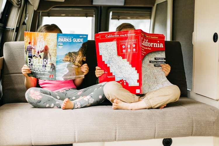 kids reading maps while camping