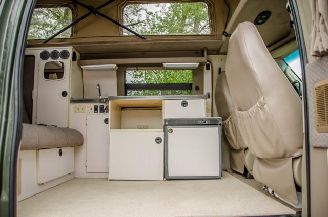 Kitchen with fridge and sink inside a 2wd Ford Econolibe Sportsmobile for sale in Portland, Oregon through Roamerica camper van rental company