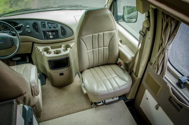 Front swivel seat inside a 2wd Ford Econolibe Sportsmobile for sale in Portland, Oregon through Roamerica camper van rental company