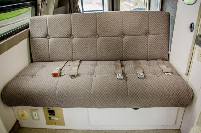 Sofa bed and bench seat with 3 seat belts inside a 2wd Ford Econolibe Sportsmobile for sale in Portland, Oregon through Roamerica camper van rental company