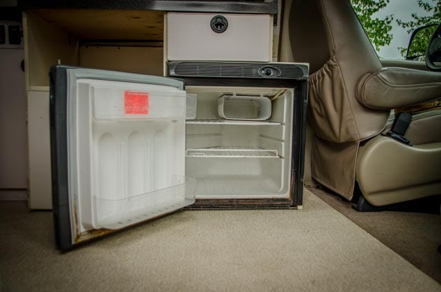Fridge and freezer inside a 2wd Ford Econolibe Sportsmobile for sale in Portland, Oregon through Roamerica camper van rental company