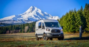 Exterior shot of front side of Ford Transit Campervan with Mt. Hood in background built by Axis Vehicle Outfitters in Portland, Oregon