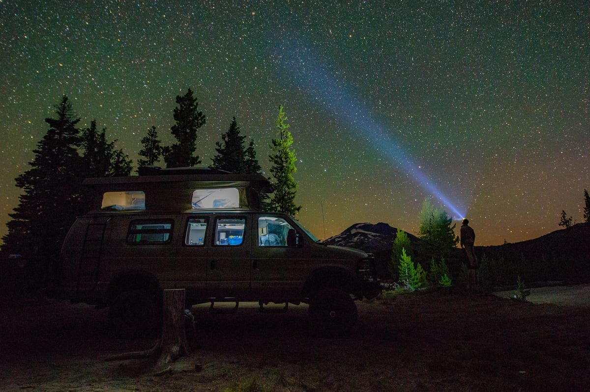 Coast headlamps from Portland, Oregon help illuminate the night sky near Mt. Hood with a 4wd Ford Econoline Sportsmobile and pop top in the background