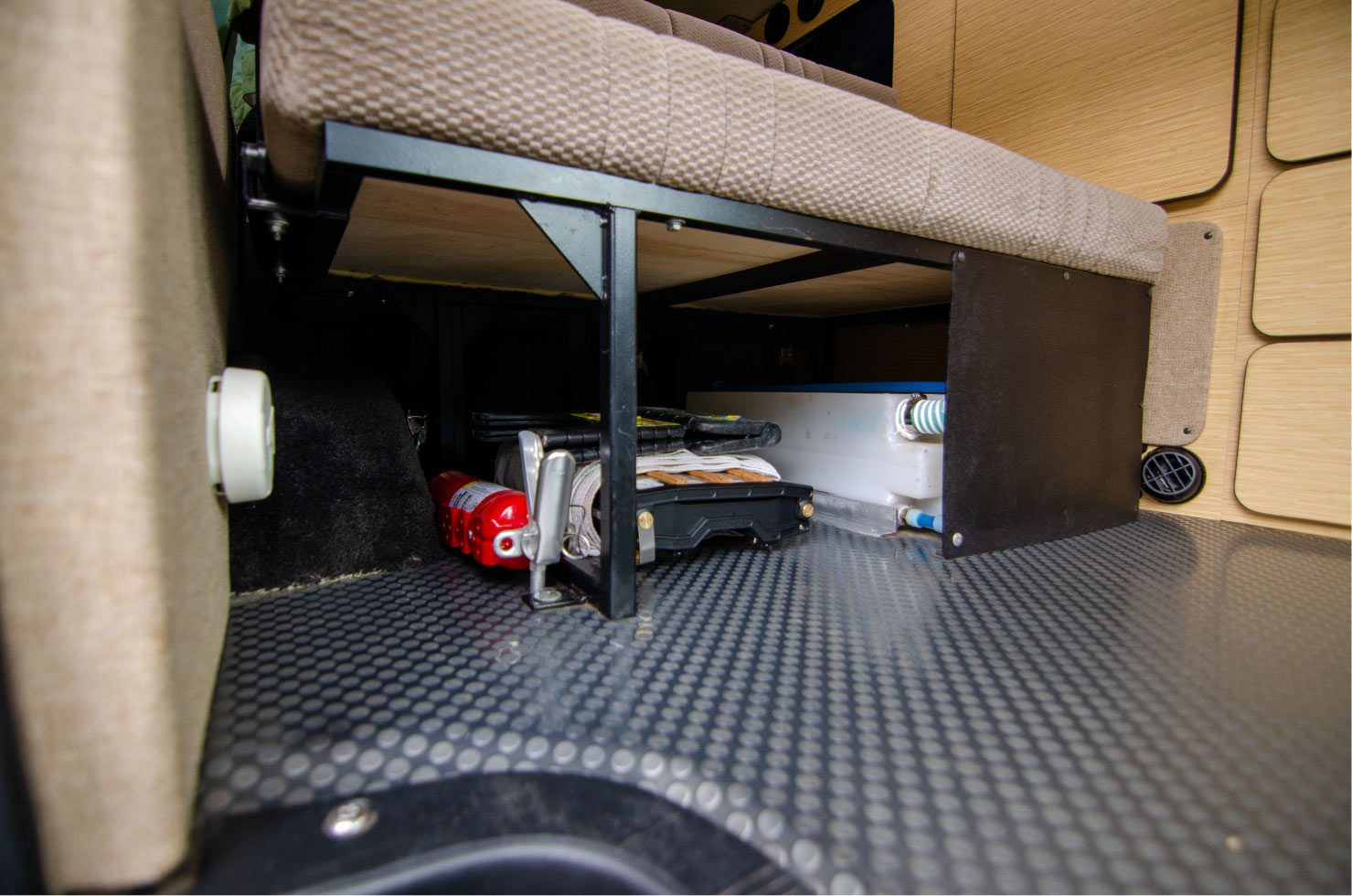 Underneath the sofa bed bench seat on a Ford E-Series 4x4 Econoline Sportsmobile RB50 Layout Campervan conversion for sale. Shows the water tank.