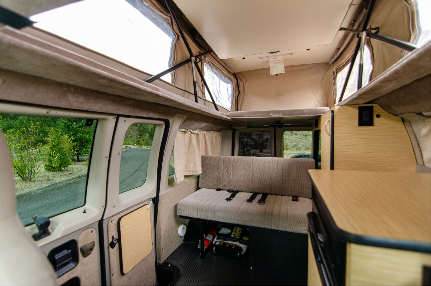 Inside view of a 4wd Sportsmobile penthouse with windows that open with screens Ford E-Series 4x4 Econoline Sportsmobile RB50 Layout Campervan conversion for sale built by Van Specialties