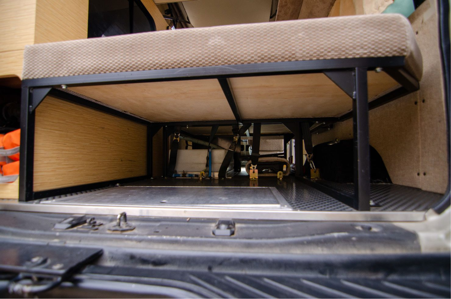 rear view of under sofa bed in a 4wd Sportsmobileon a Ford E-Series 4x4 Econoline Sportsmobile RB50 Layout Campervan conversion for sale built by Van Specialties