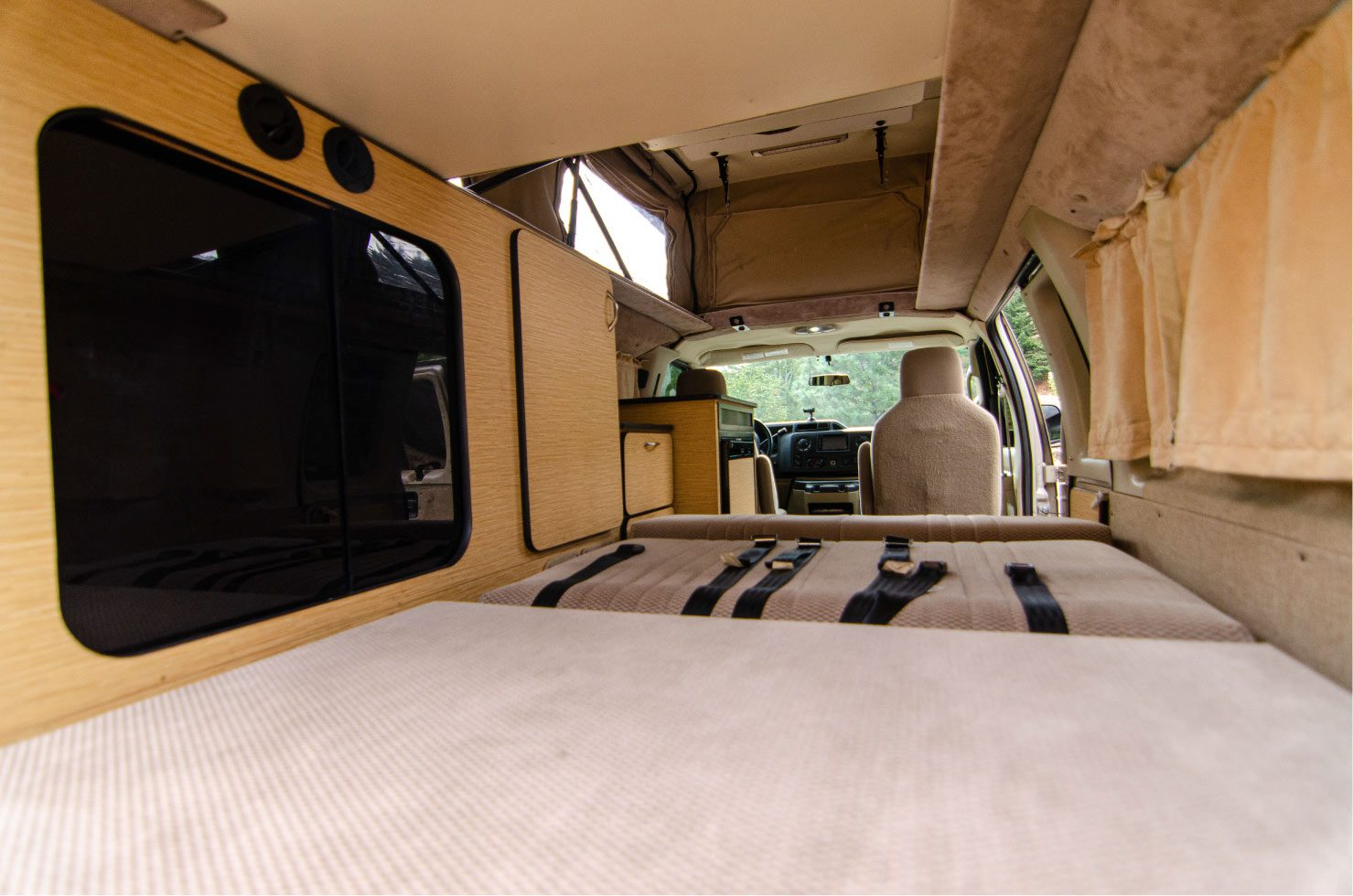 Full closet inside a Ford E-Series 4x4 Econoline Sportsmobile RB50 Layout Campervan conversion for sale built by Van Specialties
