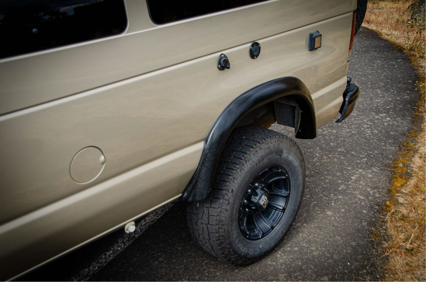 Tires, wheels, shore power and water hook up on a Ford E-Series 4x4 Econoline Sportsmobile RB50 Layout Campervan conversion for sale built by Van Specialties